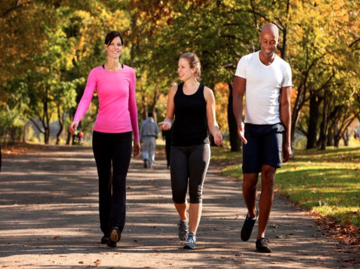 three people exercising in a park